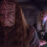 worf in his religious attire is in the foreground looking conflicted as a priest in the background looks on